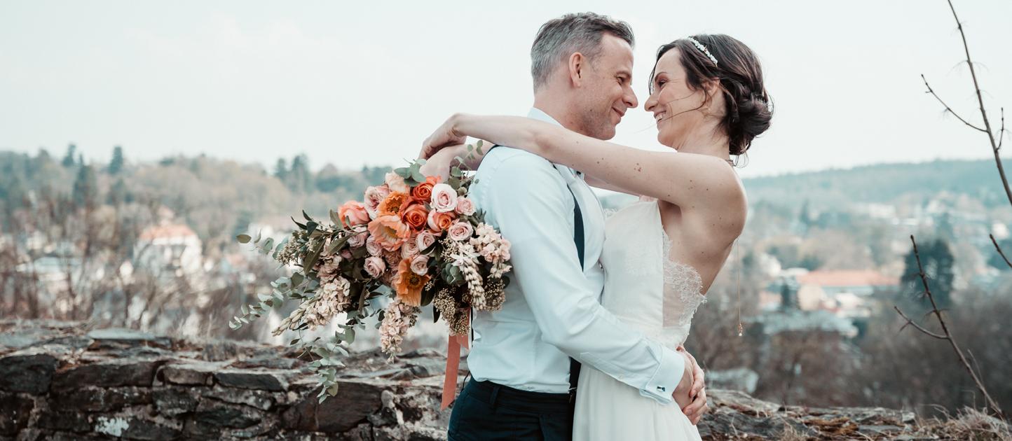 Brautpaar mit Brautstrauß bei der Umarmung.
